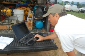 Steve Crandall checks readings on a laptop from the newly installed wind turbine.