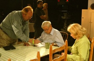 Ralph Waite (center seated) who played John Walton in the series and Michael Learned (right) who played Olivia Walton, go over notes with a member of the production staff during the shooting of the reunion series.