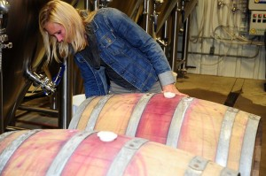 ©™2013 Blue Ridge Life: Photos By BRL Mountain Photographer Paul Purpura : Emily Pelton, winemaker at Veritas Vineyard and Winery in Afton inspects one of the two barrels she supplied to Wild Wolf earlier this week as part of a special collaborative brew using kombucha cultures, additional barrels from Pollak Vineyards, and the gang at Barefoot Bucha.