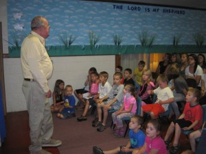 Photo Courtesy of Piney Mountain Ministries Facebook Album : Mr. Robert Mansfield on July 21, 2014 during Vacation Bible School speaking with children.