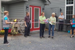 Flanked by Frank Ott's grandchildren on the far right and left, Wintergreen F&R Chief Curtis Sheets L) looks on as Julia Rogers (Nelson Chamber President - center) and Nelson BOS Chair Connie Brennan cut a ribbon officially dedicating the newly renovated fire station in the late Frank Ott's name.