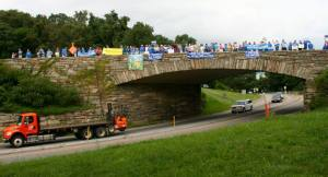 Photo courtesy of Free Nelson: Passing cars honk their horns in support of the dozens of people stretched across the stone bridge over Route 250 where the Blue Ridge Parkway crosses. Tuesday - August 18, 2015