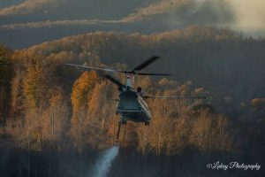 Photo courtesy of Debbie Wilson - Lukey Photography - Piney River, Virginia : A firefighting helicopter and crew take off after dipping water from Thrashers Lake earlier this week to battle the wildfires in Amherst County, Virginia