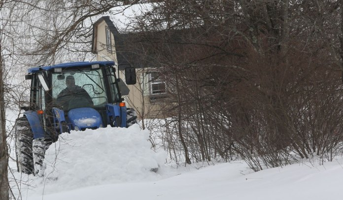 Lauren Yoder plows a driveway near Sandy Flats road.