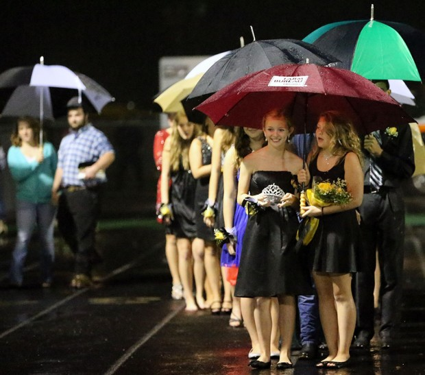 The homecoming court waits under umbrellas for start of the half-time festivities.