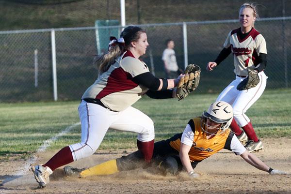 Sliding under the tag at third base.