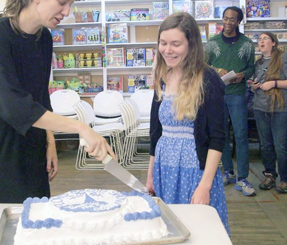Anna Roberts-Gevalt (left) cuts a cake honoring the time she and Elizabeth Leprelle (right) at The Floyd Radio Show.