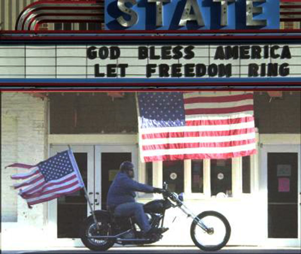 A photo captured my chance at the State Theater in Falls Church, Virginia, after the terrorism attacks on September 11, 2011. I had dropped my wife off a doctor's appointment and saw the flag at the theater and decided to shoot the photo. The motorcyclist came by just at that moment.