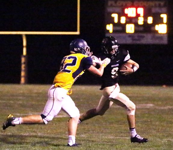 Buffaloes quarterback Ian Bary keeps the ball to gain yardage.