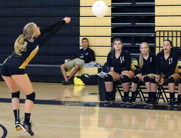 Jenna Weeks sets up a return as the Floyd County JV bench watches the action.