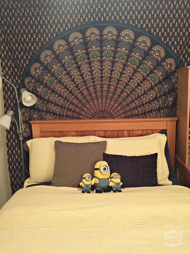 Hanging a tapestry over the bed that featured her navy & yellow color scheme helped liven up the apartment bedroom.