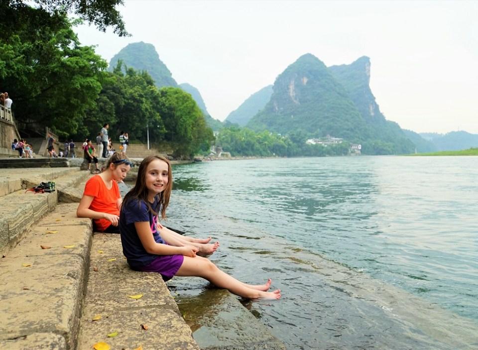 The girls dip their feet in the Li River