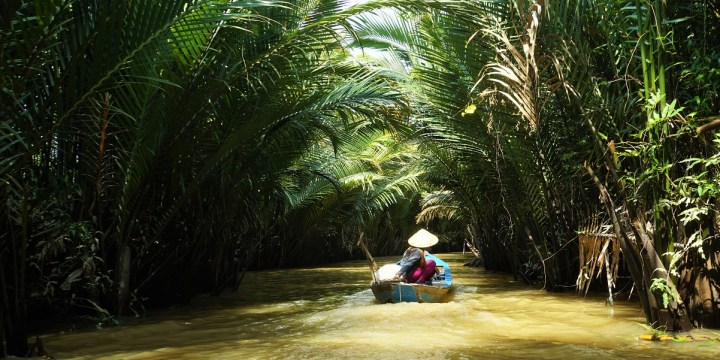 A woman plies her boat through a small canal on the Mekong Delta