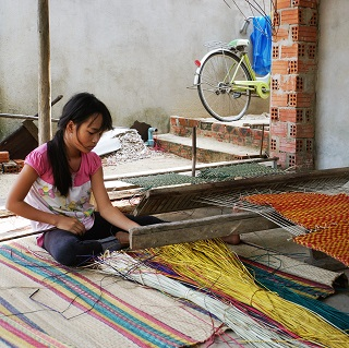 A grade 7 girl spends her Sunday morning weaving sleeping mats