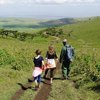 The girls follow Limon down a trail to a Maasai village