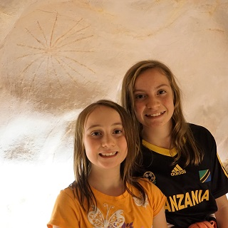 The girls stand next to a replica cave painting inside a diorama
