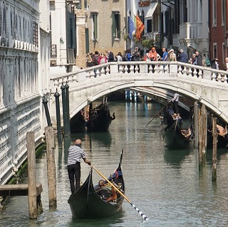 Gondoliers steer their boats under the Bridge of Sighs