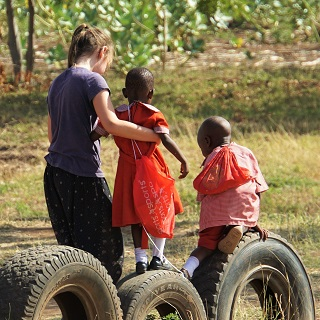 Claire plays with kids in the school's makeshift playground