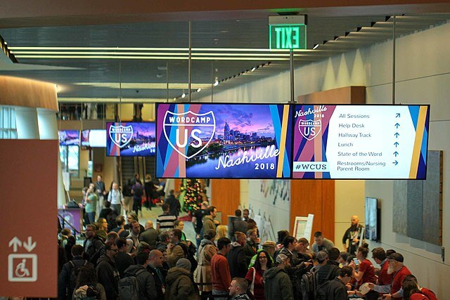 Beautiful digital signage is shown on wayfinding screens high above a crowded conference center hall.