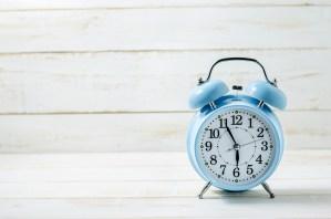 Blue Vintage Alram Clock on white wooden table