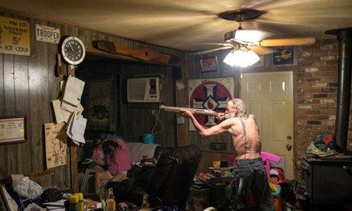 Carl, an Imperial Wizard of a southern-based Ku Klux Klan realm, takes aim with a pellet gun at a large cockroach (on the piece of paper just below the clock) while his wife and goddaughter try to avoid getting struck by a possible ricochet. Photo by Anthony S. Karen