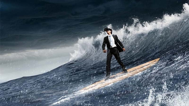 Young handsome businessman balancing on surfing board. Mixed media
