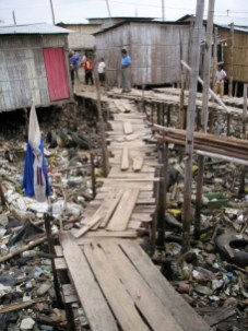 In Ecuador, the only way to visit homes over the sewage dump was to walk this rickety plank over raw sewage
