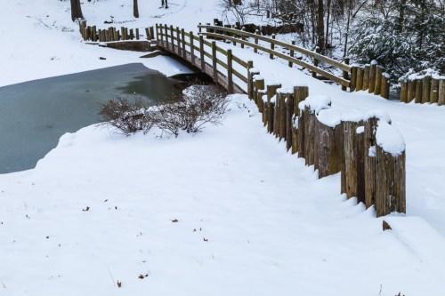 Snow covered bridge over frozen stream, Burns Park, Arkansas