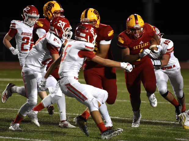 Skyline's Mike McKrola, right, carries the ...