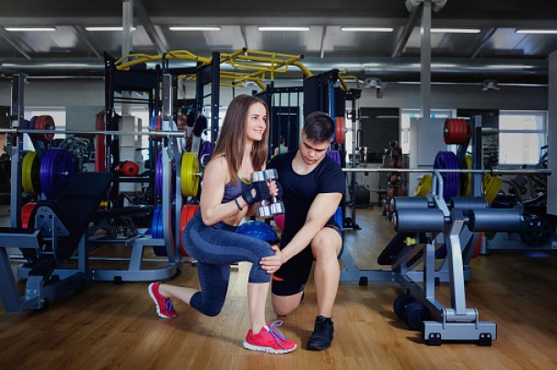 Personal trainer instructor helps to do exercises for sports gi