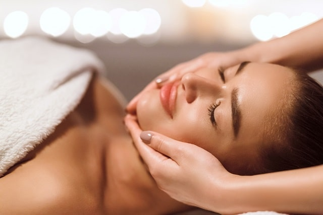 facial beauty treatment woman getting face massage HRWD5FB scaled min