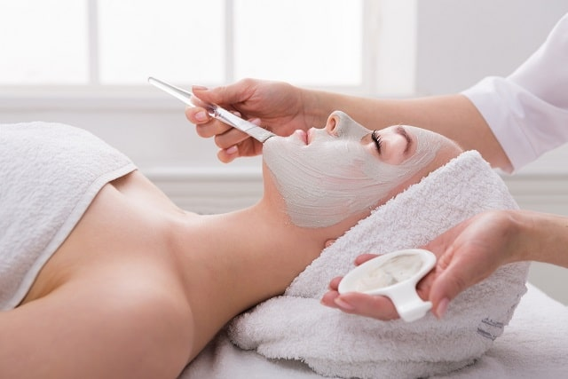 woman gets face mask by beautician at spa YVN56QS 1 scaled min