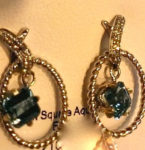 Square cut Aquamarine gemstones shine in a suspended circular earring design, set in 14kt. yellow gold. $675