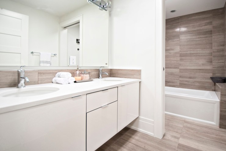 Livingstone bathroom completed, with wooden white marble installed on floors, backsplash and walls