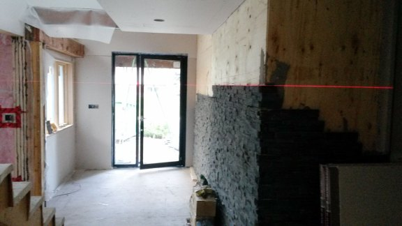 Livinstone Entrance mid construction (jet black slate ledgestone, 1/2 installed, glass entrance doors)
