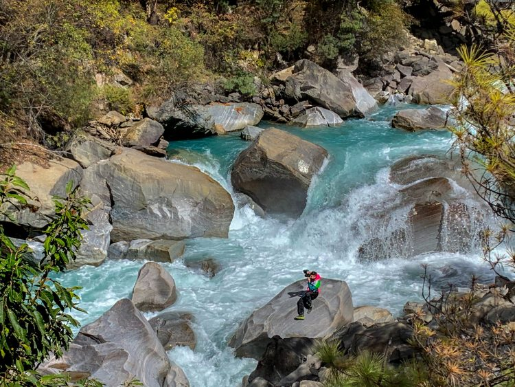 Liviu pe un bolovan mare la râu, fotografiind podul de deasupra