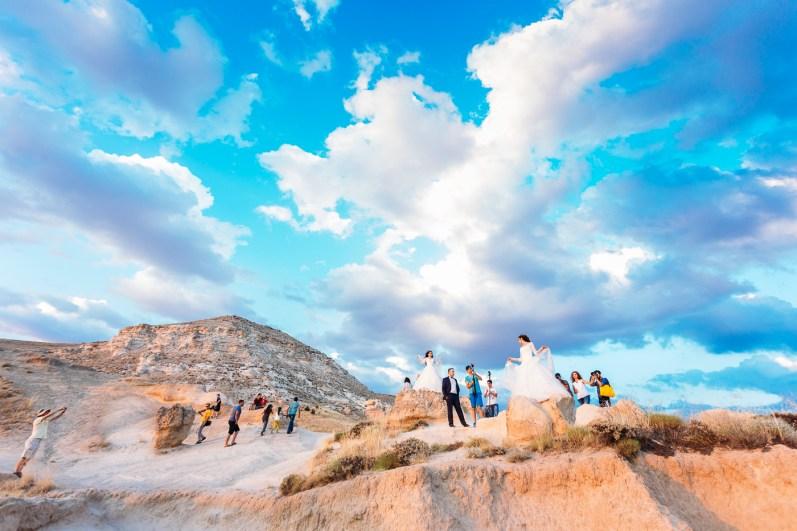 Brides get their photos taken at sunset point in Cappadocia