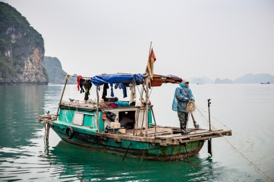A fisherman pulls in her net in Bai Tu Long Halong Bay