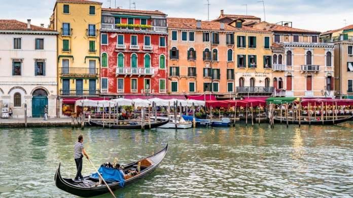 Gondoleiro remando na gôndola no grande canal em Veneza, Itália.