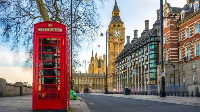 A icônica caixa de telefone vermelha britânica antiga, com o Big Ben ao fundo, no centro de Londres - Inglaterra
