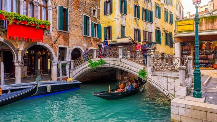 Canal estreito, com gôndola e ponte em Veneza, Itália.