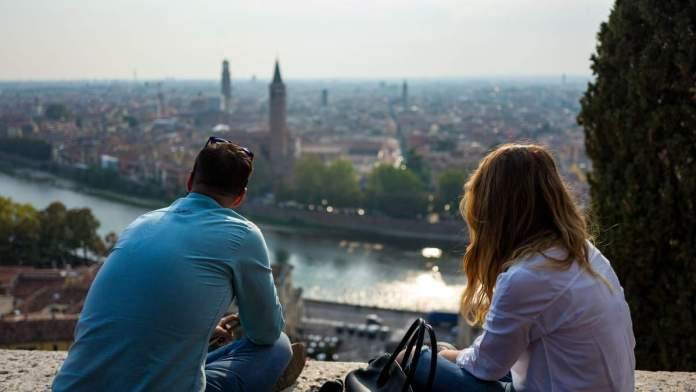 Casal desfrutando da bela vista de Verona, Itália.