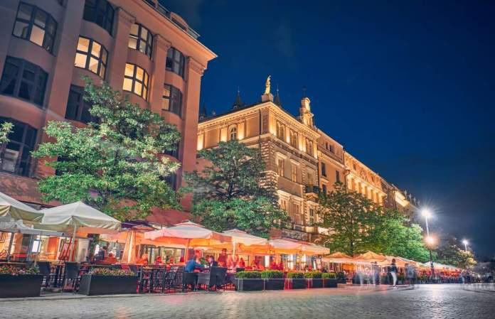Cafés e restaurantes na praça principal à noite em Cracóvia, Polônia
