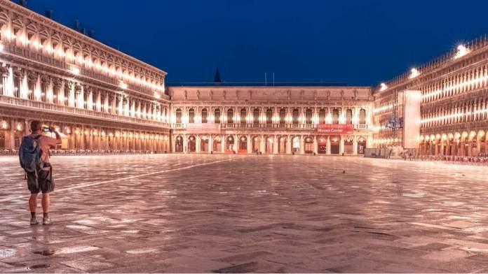 Turista tirando fotos na praça San Marco à noite, em Veneza - Itália.