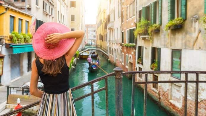 Mulher aprecia a vista de um canal com passagem de gôndola em Veneza, Itália.