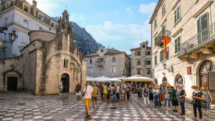 Os turistas se reúnem na praça de São Lucas, em frente à igreja antiga, com suas três torres sineiras em Kotor, Montenegro.