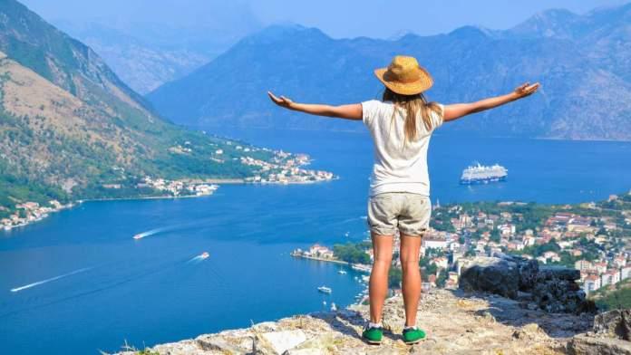 Mulher jovem turista, desfrutando de uma vista da Baía de Kotor, Montenegro.