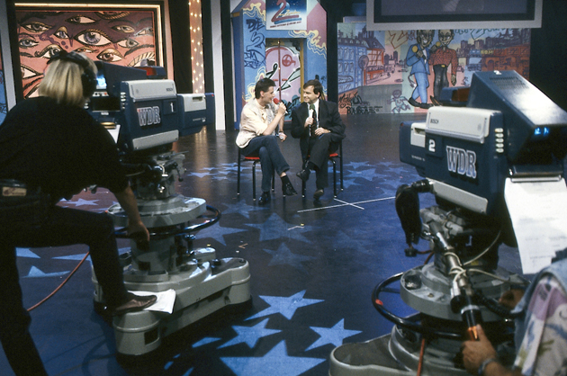 Günther Jauch & Thomas Gottschalk in front of a artwork Graffiti on canvas for the TV show »Die 2 im Zweiten« live at IFA Internationale Funkausstellung, Berlin 1991. © ZDF Barbara Oloff