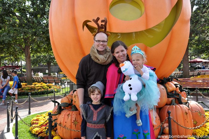 Family in Frozen costumes in front of pumpkin