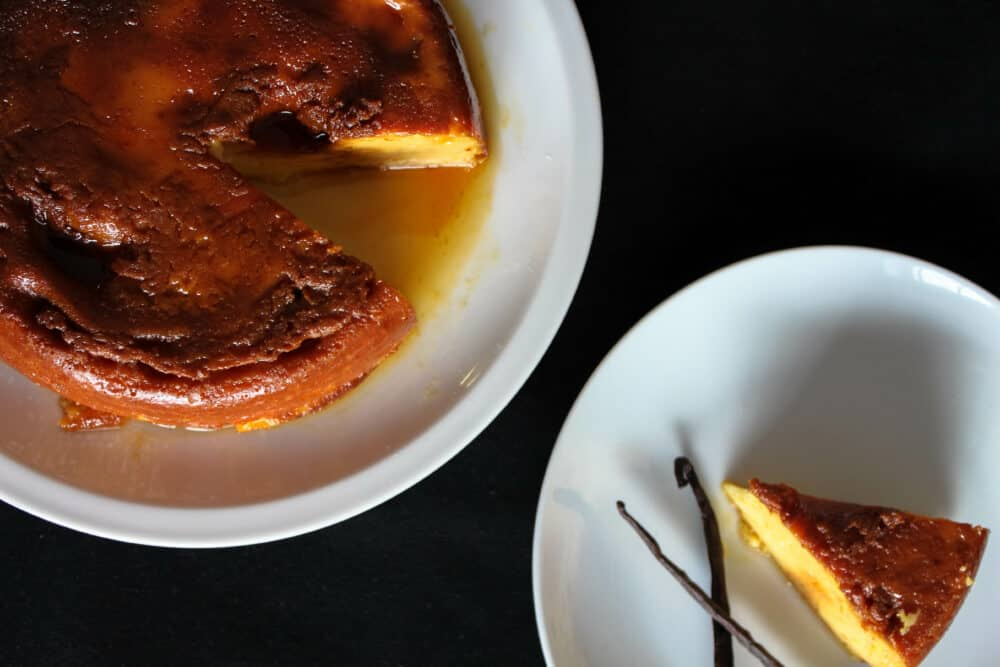 From above, Cuban flan in a white plate and a slice on the side.